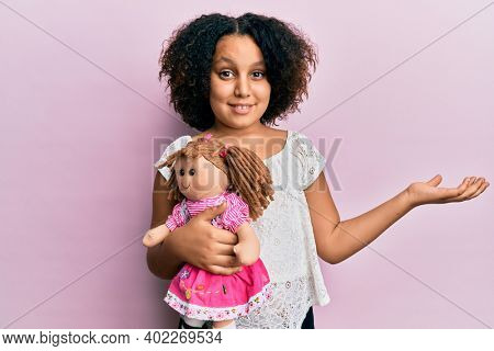Young little girl with afro hair holding animal doll toy celebrating achievement with happy smile and winner expression with raised hand