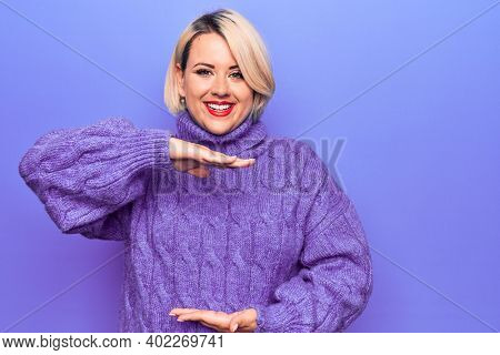 Beautiful blonde plus size woman wearing casual turtleneck sweater over purple background gesturing with hands showing big and large size sign, measure symbol. Smiling looking at the camera. Measuring