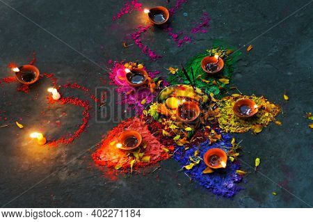 Multicolored Flower Shaped Composition Of Natural Paints, Candles And Petals Against Dark Background