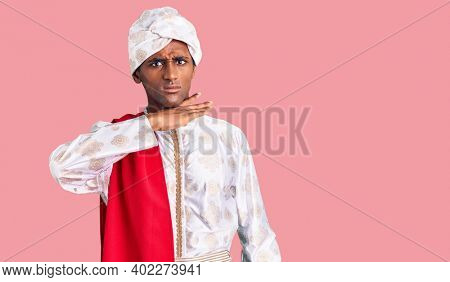 African handsome man wearing tradition sherwani saree clothes cutting throat with hand as knife, threaten aggression with furious violence