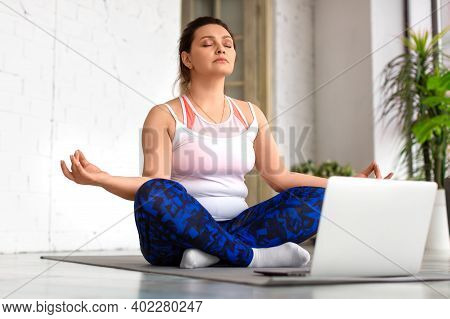 Woman With Closed Eyes Meditate In Front Of Laptop In Home Interior. Yoga And Healthy Lifestyle Conc