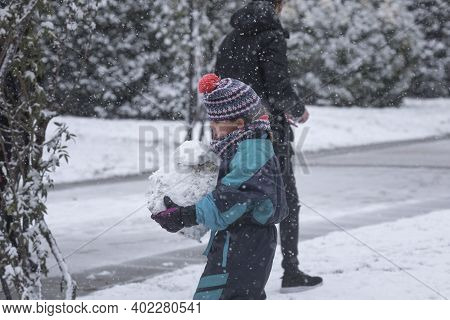 Madrid, Spain - January 07, 2021: Children Playing With Snow And Making Snowmen, In The Buen Retiro
