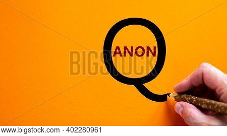 Q Anon Symbol. Hand Writing Words 'q Anon', Isolated On Beautiful Orange Background. Business And Q
