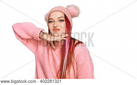 Young caucasian woman wearing casual clothes and wool cap cutting throat with hand as knife, threaten aggression with furious violence
