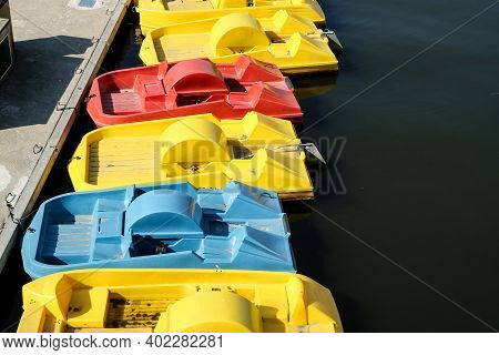 Several Empty Colorful Paddle Boats Standing On The Water By The Pier At The Riverside. Amusement Fo