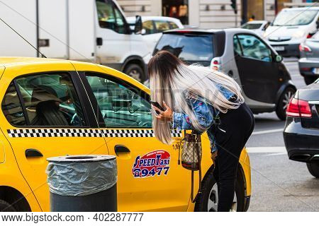 Girl Asking Taxi Driver If Available For A Ride. Taxi Car Parked At The Taxi Station In The Capital