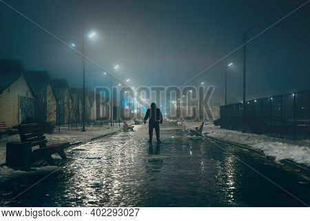 Silhouette Of Dark Man In Hood In Night Illuminated City Alley In Foggy Weather, Misty Horror And Sc