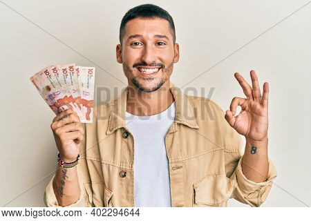 Handsome man with tattoos holding 10 colombian pesos banknotes doing ok sign with fingers, smiling friendly gesturing excellent symbol
