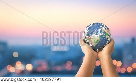 Donation For Covid 19 Concept:  Human Hands Holding Earth Global Over Blurred City Night Background.