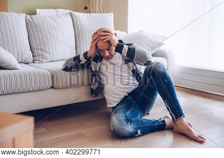 A Worried Man Is Sitting On The Floor Holding His Head.