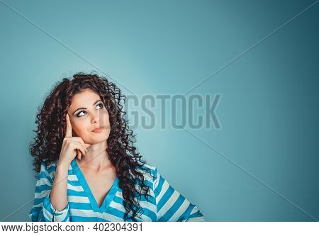 Portrait Close Up Of Happy Beautiful Young Woman Thinking Looking Away, Up Isolated Blue Wall Backgr