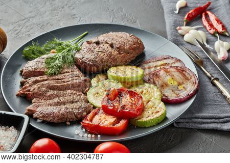 Roasted meat. Grilled beef steak and vegetables with spices on gray slate  background. Setting table. Steak menu. Grilled menu.