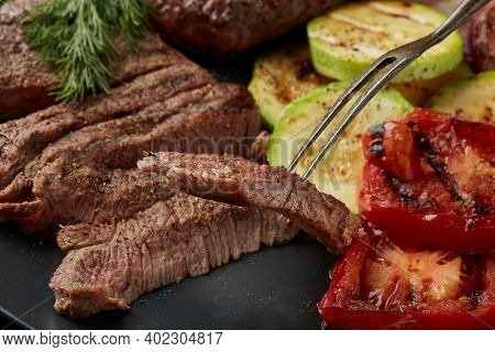 Roasted meat. Grilled beef steak and vegetables with spices on gray plate.   Selective focus on slice of meat on fork. Steak menu. Grilled menu.