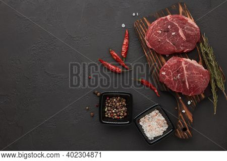Raw fresh meat. Beef steaks on cutting board and spices on black slate background. Top view with copy space. Steak menu