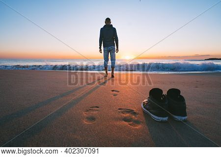 Carefree Barefoot Man Going To The Sea Or The Ocean Without Shoes On Sunset. Concept Of Freedom. Enj