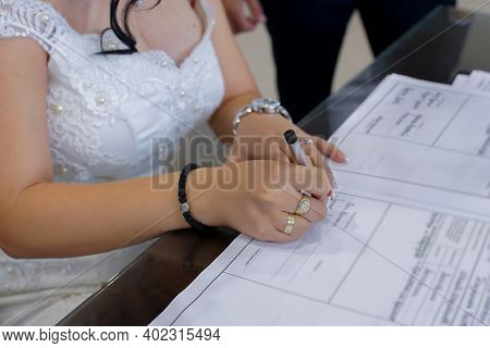 Woman Signing Marriage Contract. Wedding Concept In Restaurant