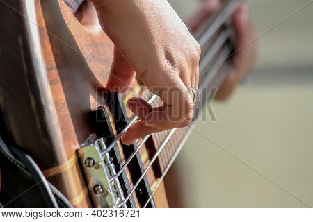 Selective Focus To Asian Woman\'s Hands Playing Bass Guitar. Close Up Girl Musician\'s Hands Playing