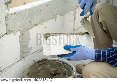 Construction Worker Puts Foam Concrete Bricks Into The Wall In The House Under Construction,building