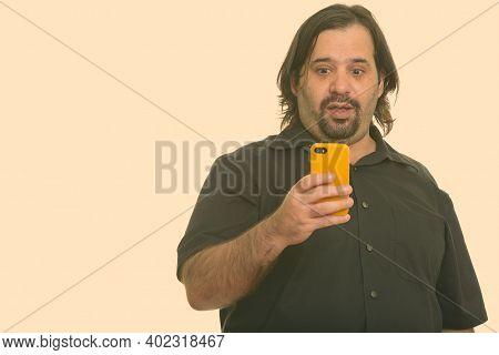 Fat Caucasian Man Using Mobile Phone Looking Shocked