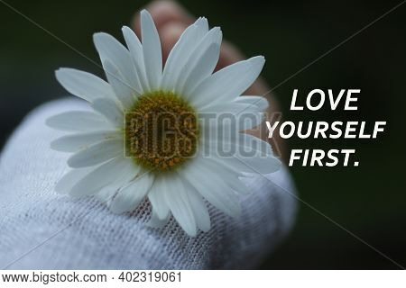 Inspirational Quote - Love Yourself First. On Floral Background Of White Daisy Flower In Hand. Self