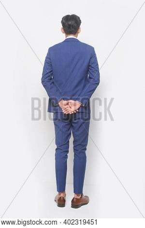 full body young businessman  wearing blue suit ,tie with white shirt and blue pants with brown leather shoes,back view