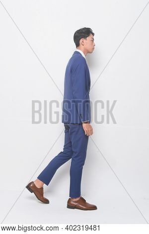 Side view full body young businessman  wearing blue suit ,tie with white shirt and blue pants holding black handbag with brown leather shoes