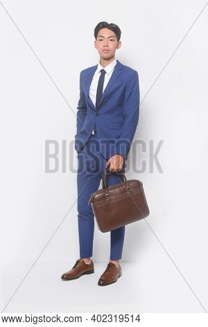 full body young businessman  wearing blue suit ,tie with white shirt and blue pants holding black handbag with sneakers shoes
