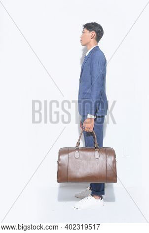 Side full body young businessman  wearing blue suit ,tie with white shirt and blue pants holding black handbag with sneakers shoes