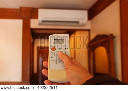 Hand Holding Air Conditioner Remote Controller Inside Bedroom
