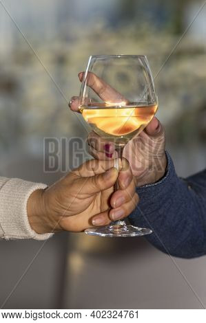 Hand Grabbing A Glass Of Wine Held By Another