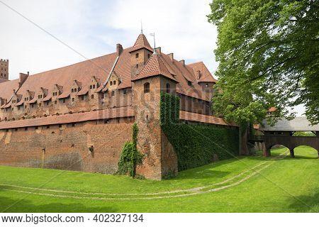 Malbork, Poland - June 25, 2020: 13th Century Malbork Castle, Medieval Teutonic Fortress On The Noga