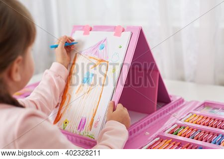 Child Girl Draws With Colored Pencils, Masking Illustration Of Her House, Using Multicolored Felt Ti