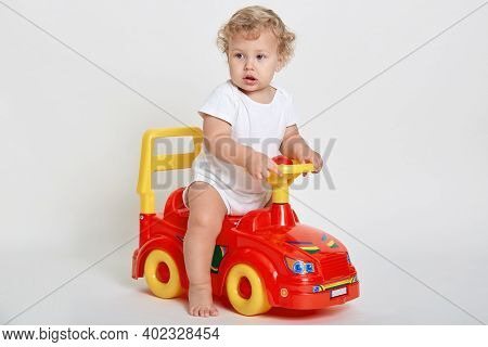 Curious Child Sitting In Toy Car And Looking Away, Sees Something Interesting Away, Having Curious F