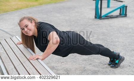 Fat Young Woman Push Up From The Bench Outdoors. A Chubby Smiling Girl Warms Up Before Jogging. Spor