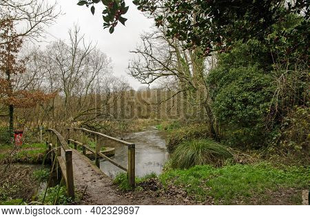 Footbridge Over A Bend In The River Itchen In The Village Of Itchen Stoke, Hampshire On A Cloudy Aut