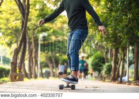 Closeup Asian Man Playing On Surfskate Or Skate Board In Outdoor Park When Sunrise Time Over Photo B