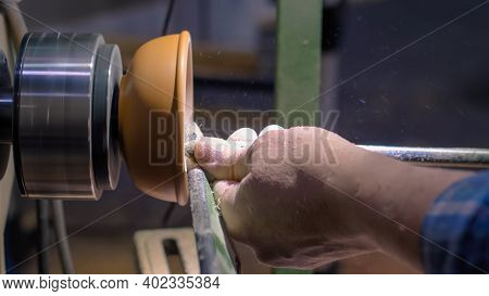 Professional Man Carpenter Holding Skew Chisel, Shaping Piece Of Wood And Using Woodturning Lathe At