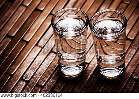 Vodka Glass On Wood. Transparent Glass Alcohol Background. Two Vodka Shots Empty Copy Space Backgrou