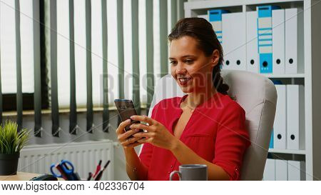 Close Up Of Freelancer Chatting And Smiling Using Smartphone. Hispanic Entrepreneur Working In Profe