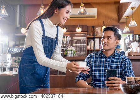 Asian Barista Of Small Business Owner Serving A Cup Of Coffee To Young Customer At The Table In Coff