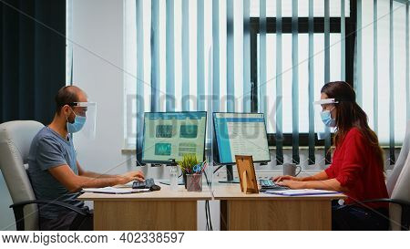 People With Mask And Visor Working In New Normal Office Checking Reports And Writing On Computer. Co
