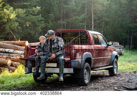 Father And Son Sitting Together In Truck Outdoors With Shotgun Hunting Gear.