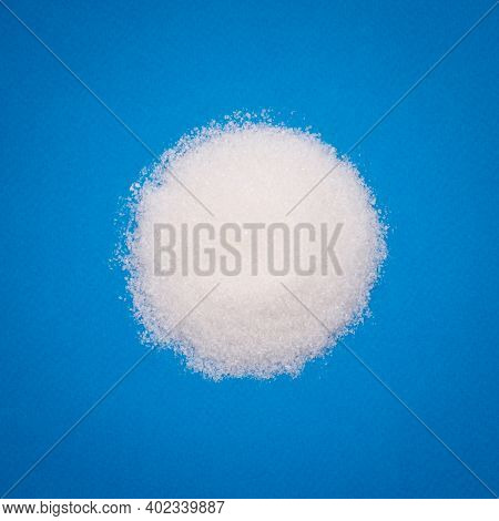 Heap Of Sugar On Blue Textured Background. Top View High Quality Photo