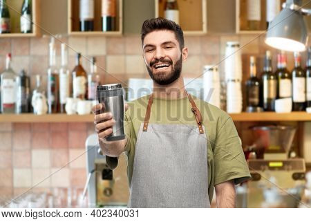 people, profession and job concept - happy smiling waiter in apron holding tumbler or takeaway thermo cup over bar background