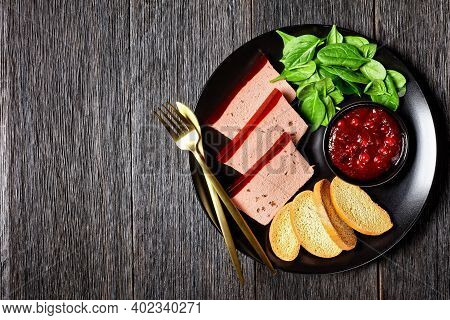 Duck Liver Pate With Cranberry Jelly On Top On A Black Plate With Cranberry Sauce, Spinach, And Brio