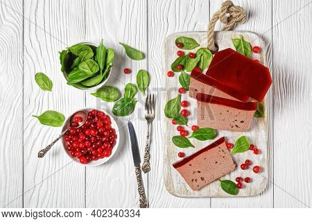 Slices Of Duck Liver Pate With Cranberry Jelly On Top On A White Cutting Board With Fresh Cranberrie