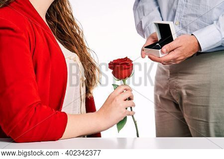 Man Giving Engagement Ring To His Partner And A Red Rose. Concept Of Valentine's Day, Couple In Love