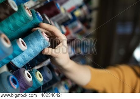 The Seamstresss Hand Takes A Skein Of Threads Of Different Colors From The Stand. A Tailor In A Sewi
