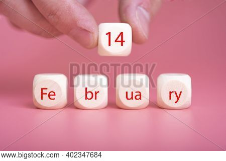 February 14 Text On Wooden Blocks And A Hand On A Pink Background.