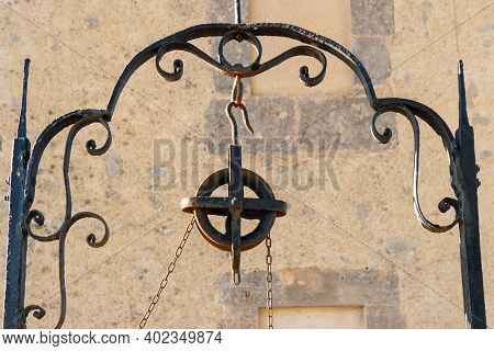 Close-up Of The Structure And The Pulley Of An Old Well Made Of Iron. Island Of Mallorca, Spain